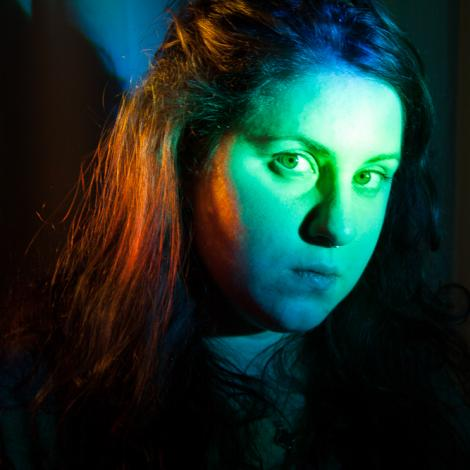 headshot of Christine Banna in front of green and orange lights