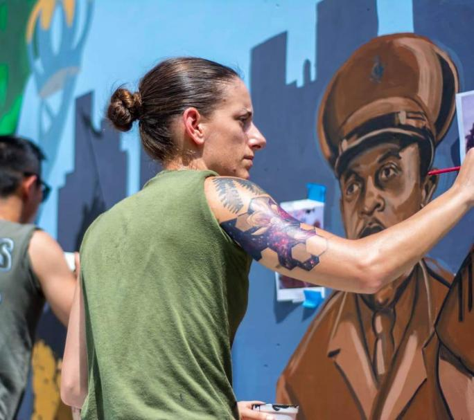 Sgt. Elize McKeley painting a mural