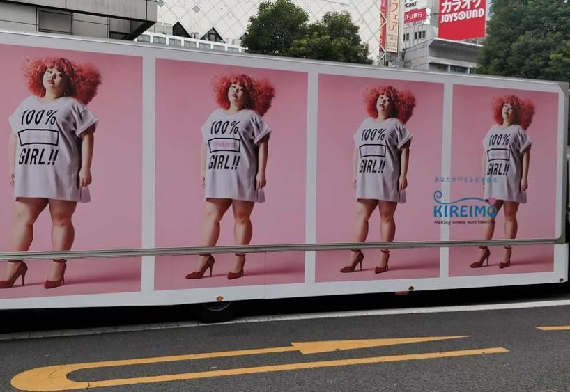 An advertisement on an 18-wheeler with a woman with red hair and a shirt that says 100% girl. Repeated four times on the truck.