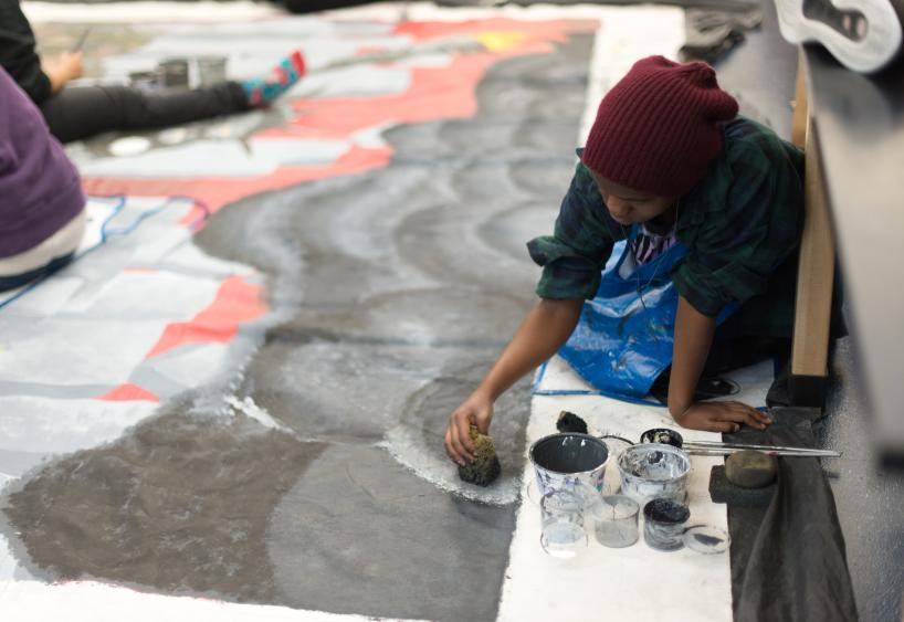 student painting a community mural