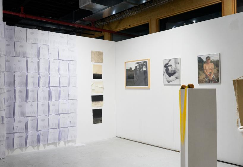gallery exhibit with papers stuck to the white wall and framed images behind pedestals
