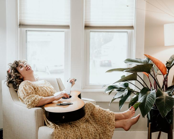 Lauren Pratt laughing in an arm chair with a guitar in her lap and a plant at her feet