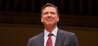 James Comey smiles while standing on the Symphony Hall stage