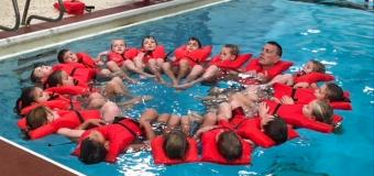 Chris Wendorf and his students in a pool all wearing safety vests and floating in a circle.