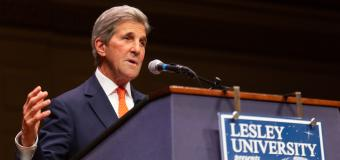 John Kerry speaks in front of a podium while gesturing with his right hand