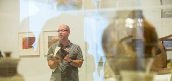 Artsy pick of Aaron Smith reading from a book, taken through a glass case at a museum.