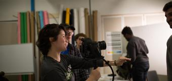 film student holds camera in classroom