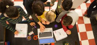 overhead view of children and teacher at table working with laptop and notebooks
