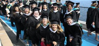 Group of graduates smiling in a group at Commencement in 2019