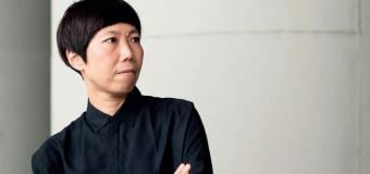 headshot of Yah-Leng Yu standing against white wall with arms crossed wearing black shirt