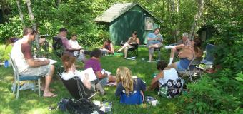 Ecological Teaching and Learning students sitting outside writing and drawing in journals