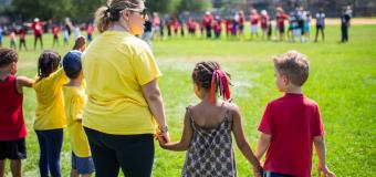 A long line of children and a teacher hold hands