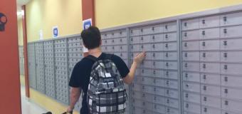 student with service dog walking by student mailboxes