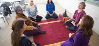 Group of women kneeling in a circle on the floor in a mindful meditation graduate class