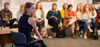 A women with long red hard sitting in a chair speaking to an audience of students