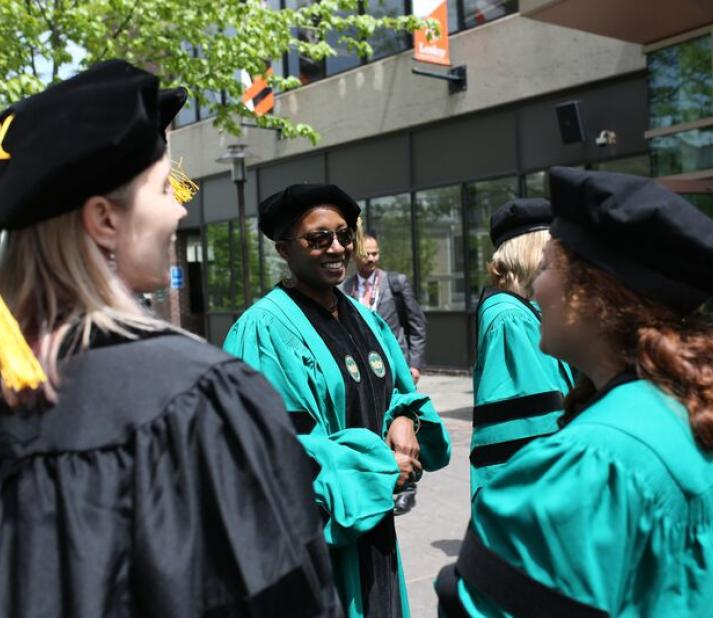 PhD students outside in caps and robes, about to attend their hooding ceremony