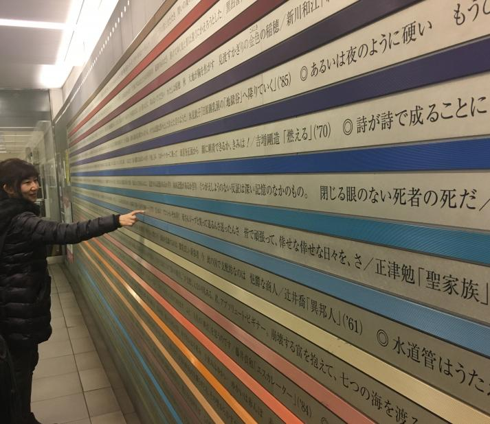 Professor Kazuyo Kubo looks at poetry printed on the walls of a subway station.