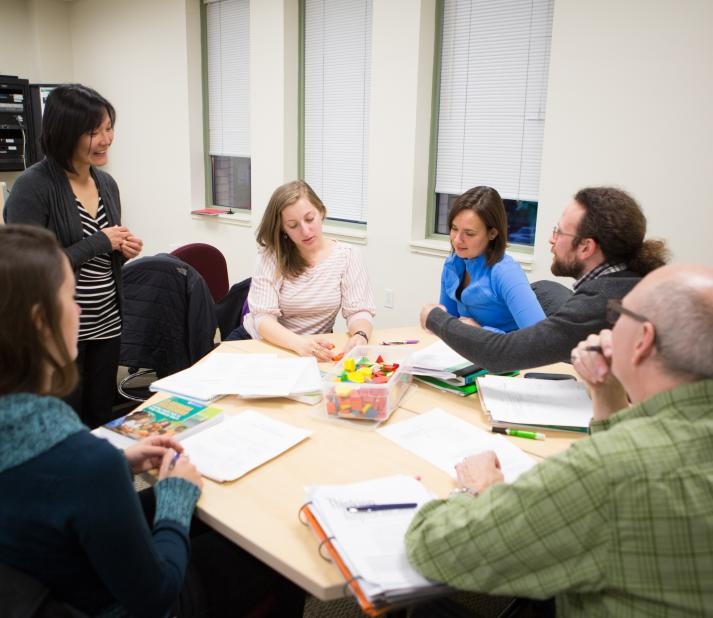 A group of adult students sit together at a round table.