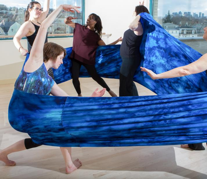 Five people pose within a large fabric wrap