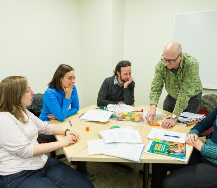 Graduate education students in a classroom with professor