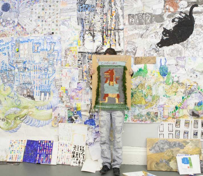 artist in studio with art covering walls