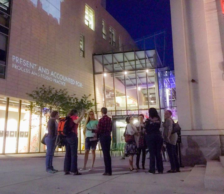 group of students standing outside the Lunder Arts Center at night