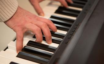 elderly hands playing a piano