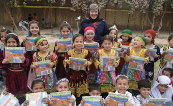Professor Louise Pascale and a group of Afghan children with their songbooks
