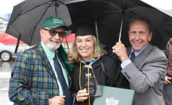 Anusia Hirsch wears her graduation robe and is stading with advisor Gene Ferraro and her husabnd under umbrellas holding her award and diploma