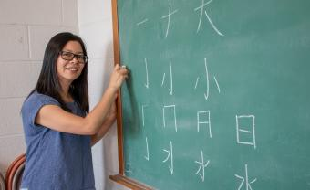Ruiming Huang teaches Chinese characters at a blackboard