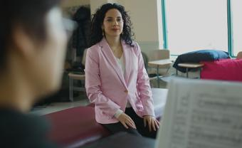 Woman in a pink blazer sitting on a bench in a classroom behind a woman playing the piano with sheet music.