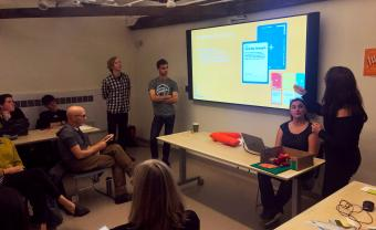 students present work on large tv screen in full classroom