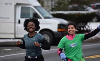 Imani Graham and Hanna Adams (who is on the right) smile and Hannah waves during a run.