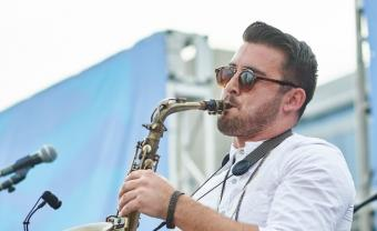 Man with sunglasses playing a saxophone on an outdoor stage.
