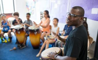 Jonathan Mande leads a drum workshop with elementary students