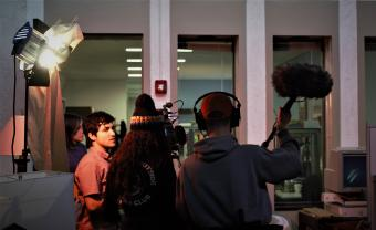 students on set with boom mic, camera, and spotlights