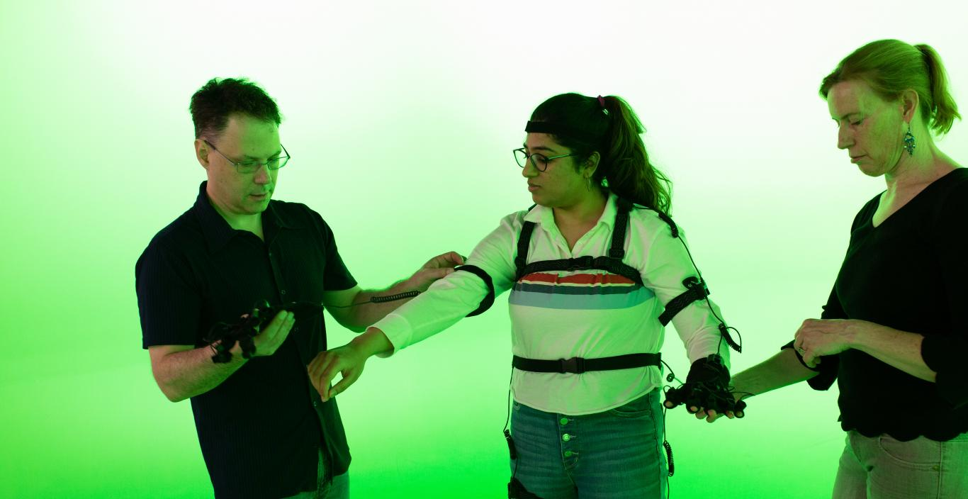 student trying out the motion capture suit in the green room with two faculty