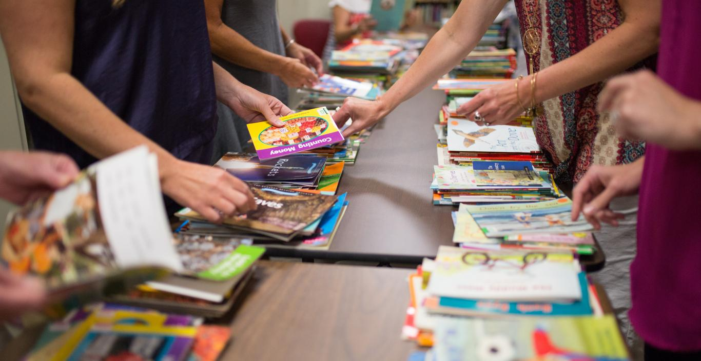 Children's books on a long table.