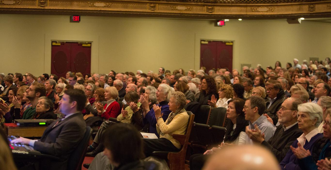 A photo of audience members seated in Symphony Hall for a Boston Speakers Series lecture.