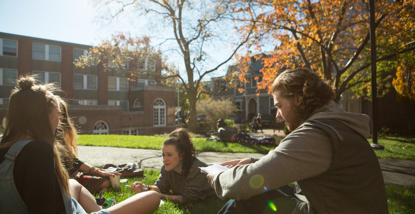 students sitting on the quad campus in the fall