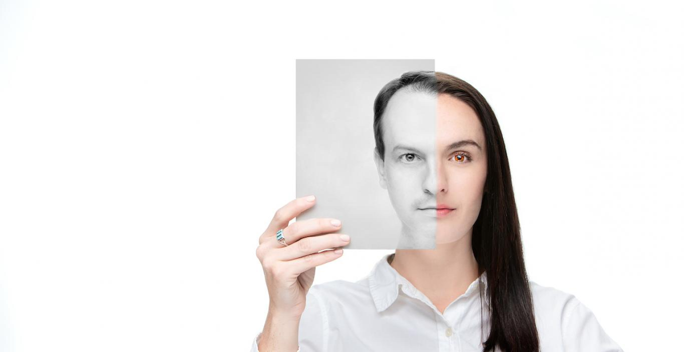 Photo of a woman with long hair half obscured by a black and white photo she is holding of herself as a man.