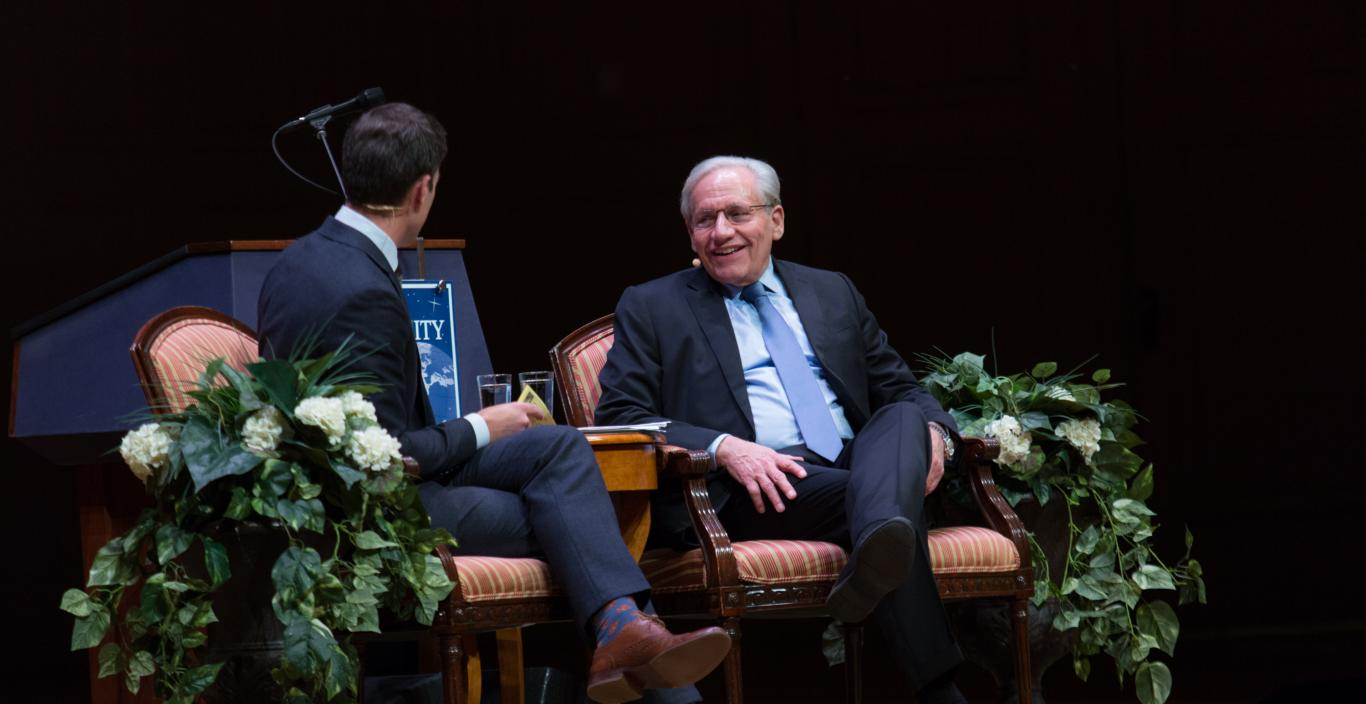 two men sitting on a stage in conversation for an interview