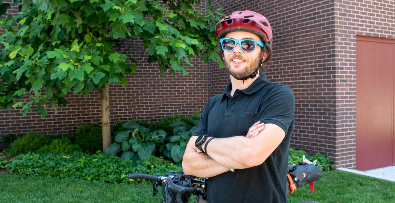 Brendan Walsh wearing his helmet and sunglasses, standing with arms crossed in front of bike.
