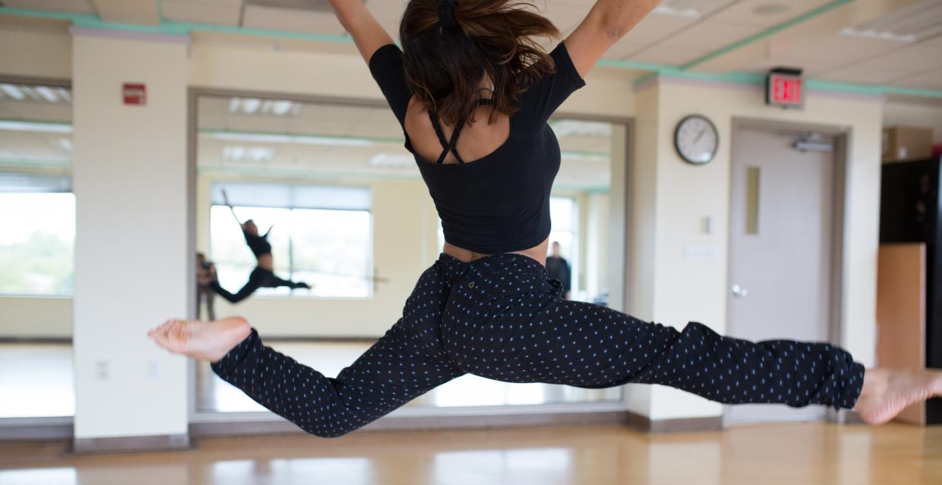 A dancer leaps in a Lesley dance studio.