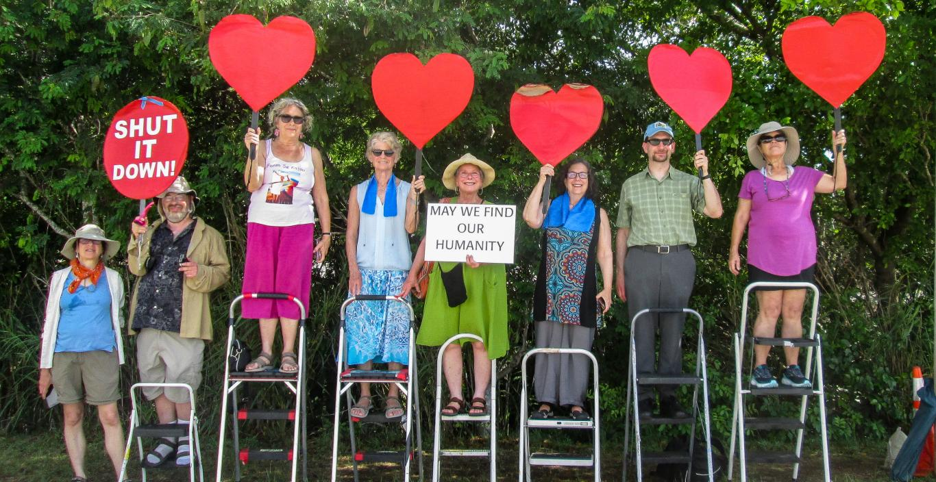 Group of people standing on step stools outside holding up red heart cutouts