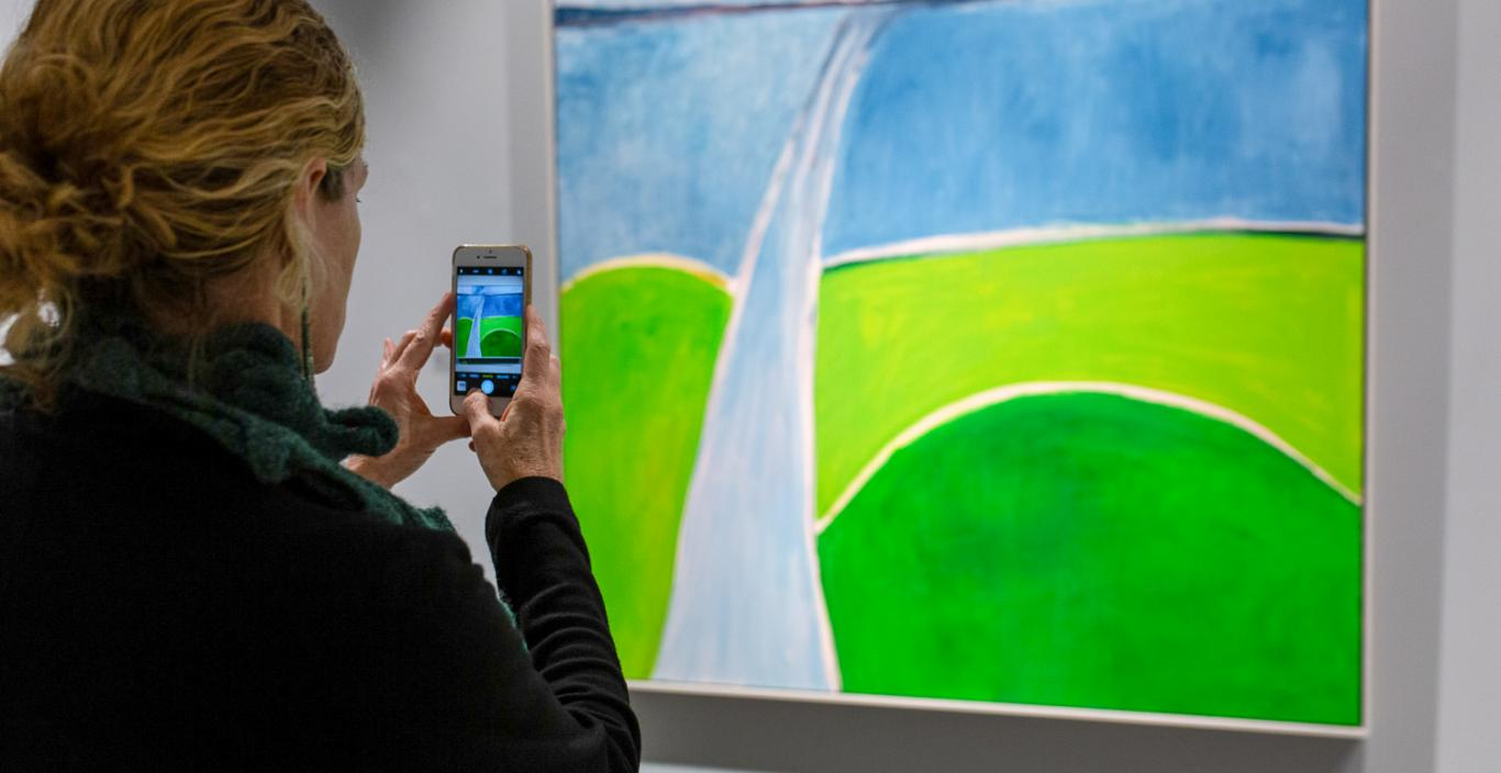 A woman takes a photo of a painting with her cell phone.