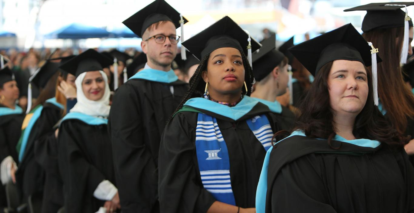 Graduate students stand at commencement
