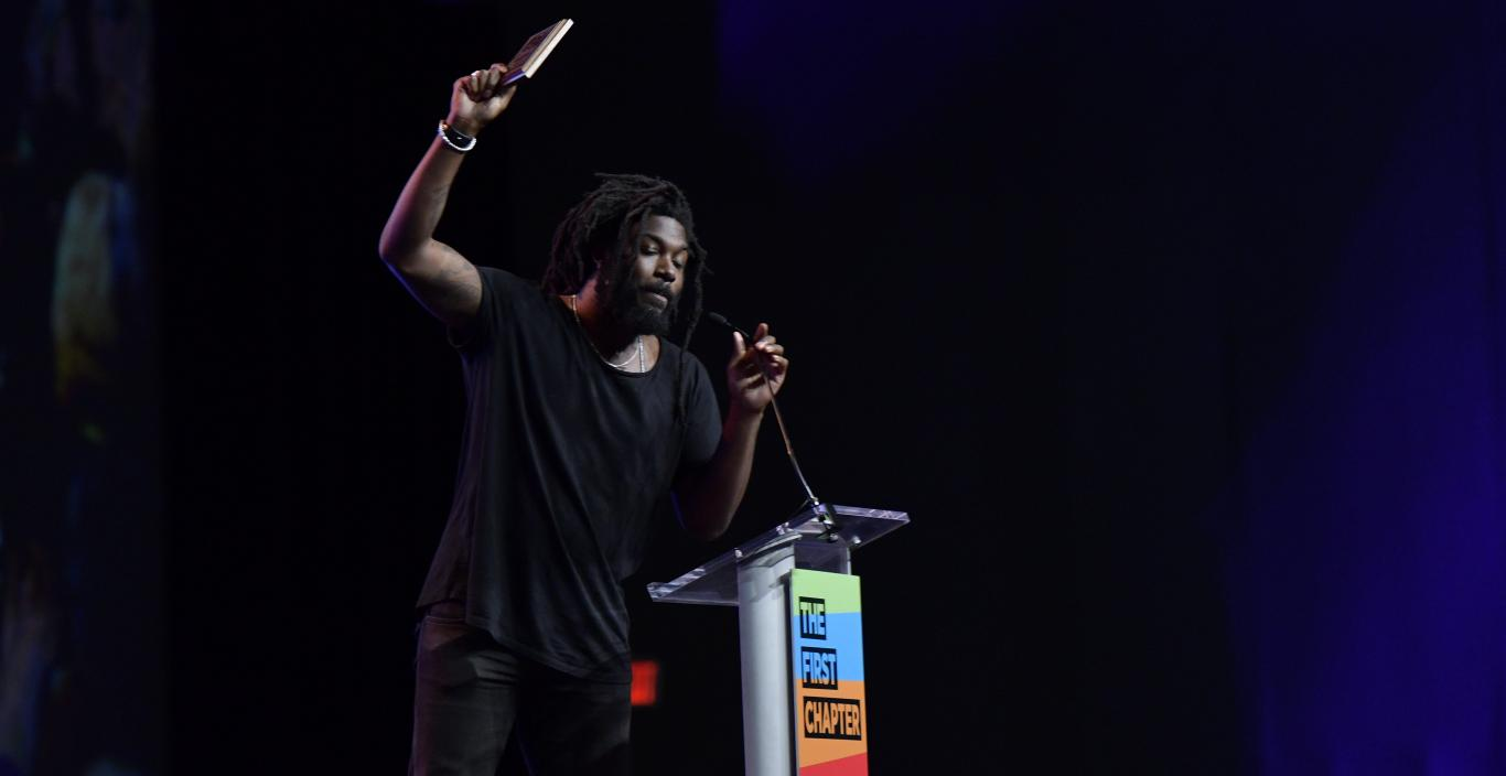 Author and creative writing faculty Jason Reynolds holds a book in the air as he speaks at the conference.