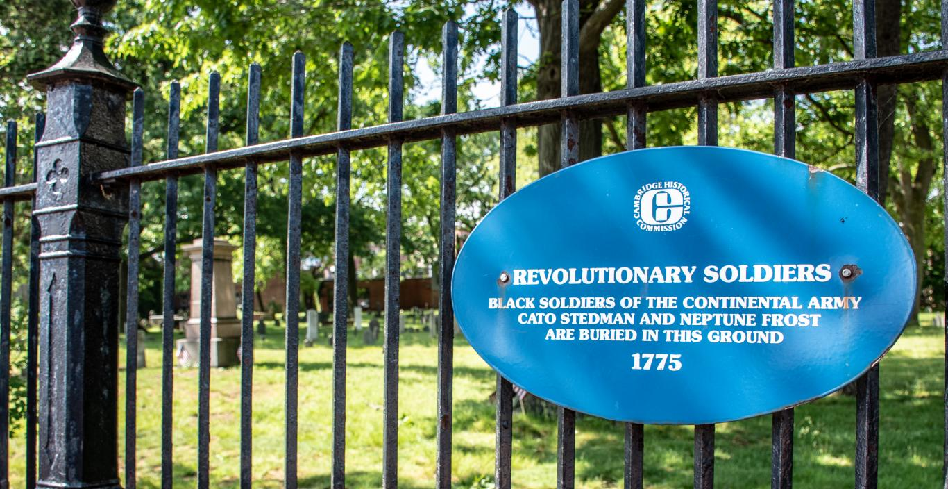 A sign on the cemetery's iron gate reads: Revolutionary Soldiers. Black soldiers of the Continental Army Cato Stedman and Neptune Frost are buried in this ground 1775.