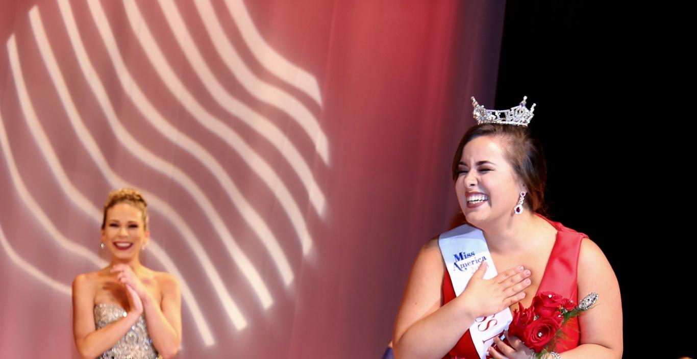 Sarah Achorn holds her hand to her heart in excitement as she wears the crown and Miss New Bedford sash on stage in her floor-length red dress.